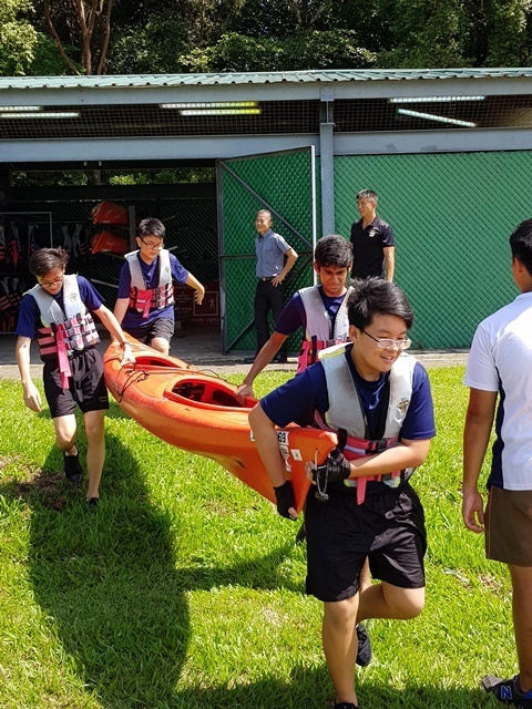 Boys team working together to carry the kayak during Sea Challenge